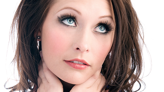 Brunette girl with long eye lashes and blue eyes looking up.