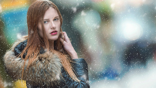 Girl with long red hair walking in the snow.