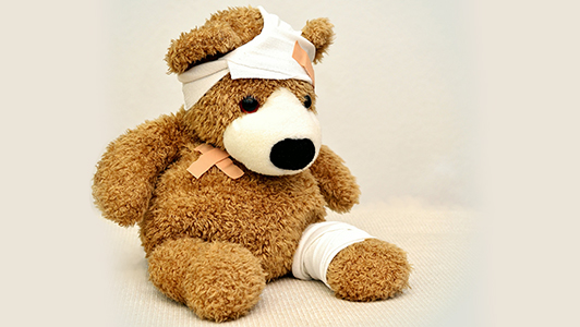 A teddy bear with patches and stitches.