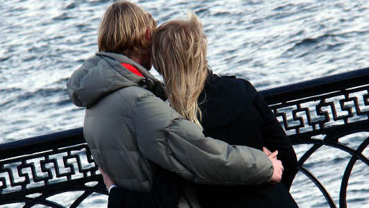 Couple hugging each other and looking at a sea.
