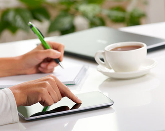 women taking notes touching smart device